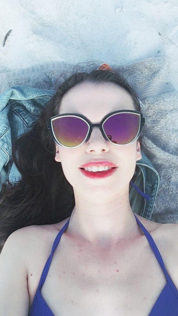jeune femme pale lèvres rouges qui bronze avec des lunettes de soleil sur la plage vue sur la ville de naples depuis une plage de floride